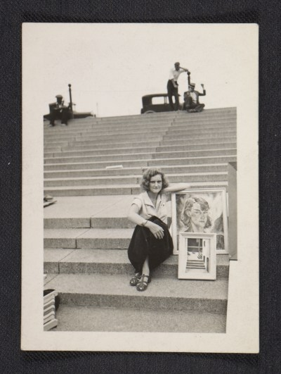 Gertrude Abercrombie sitting on steps with her artwork