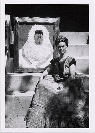 Frida Kahlo with her painting, Self-Portrait as a Tehuana