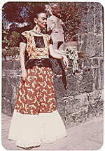 Frida Kahlo standing by a stone wall