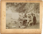 Group of seven men eating outdoors at a picnic