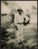 Unidentified man carrying a bundle of sticks