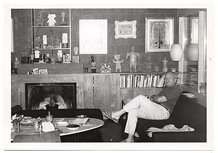 [Arnold Blanch seated near a fireplace.]