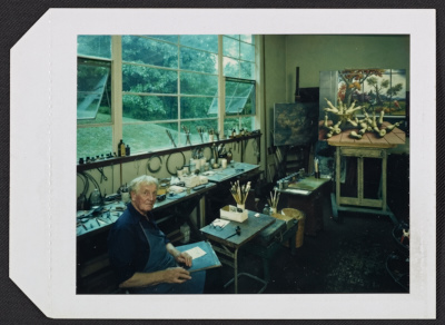 Peter Blume in his studio in Sherman, Connecticut with his painting Autumn