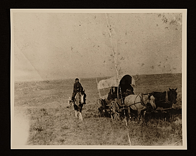 Native Americans traveling in covered wagon