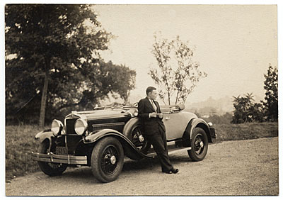 [Harry Bowden leaning on a car]