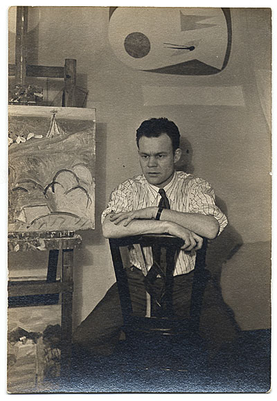 [Harry Bowden seated next to a painting.]