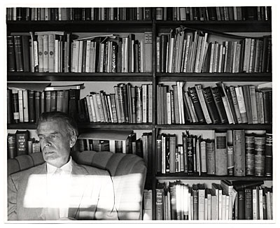 Aldous Huxley seated near bookcases