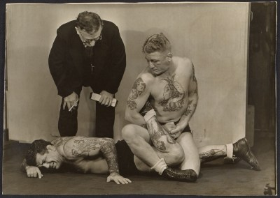 [C.J. Bulliet observing two tattooed wrestlers]