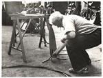 Alexander Calder marking a piece of metal