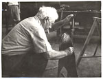 Alexander Calder inspects a piece of metal.
