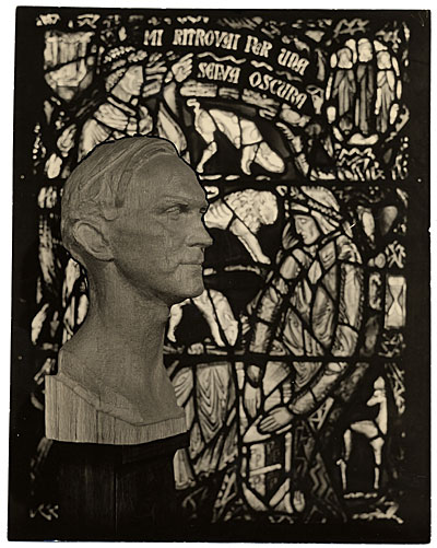[Wooden bust of Charles Connick before one of his stained glass windows]
