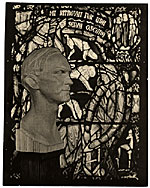 [Wooden bust of Charles Connick before one of his stained glass windows ]