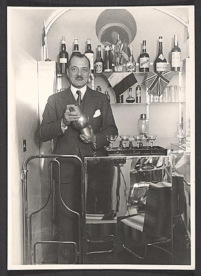 un homme en costume dans un bar, un shaker à la main