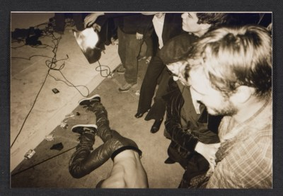 Unidentified partygoers watching a man on the floor