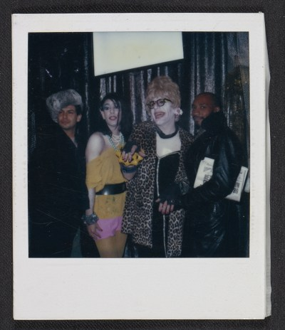 [Four unidentified people posing at a party]