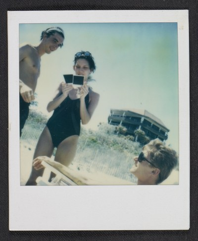 Three people at the beach, looking at polaroids