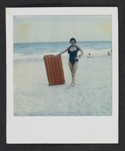 Unidentified woman posing with an inflatable raft at the beach