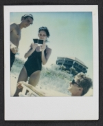 [Three people at the beach, looking at polaroids ]