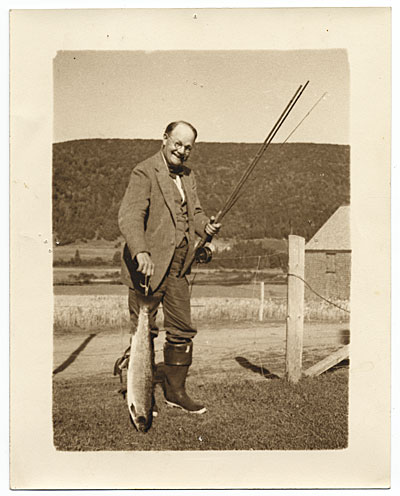 [Frank DuMond next to fence, holding a fish]