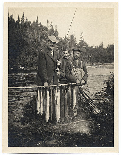 [DuMond and fishing guides holding fish]