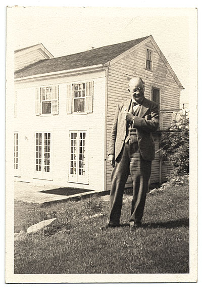 Frank DuMond standing by old farm house