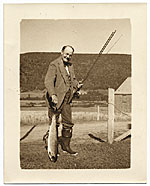 [Frank DuMond next to fence, holding a fish ]