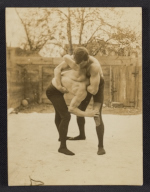 Two men wrestling in a courtyard