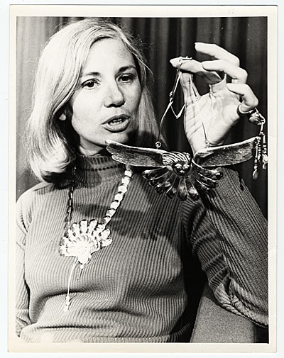 [Arline M. Fisch holding a necklace]