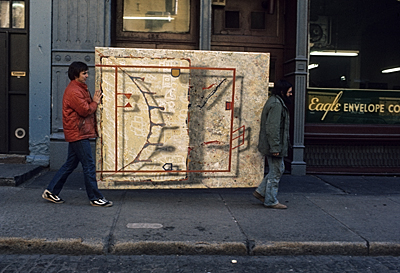 Two men carrying a painting in Soho