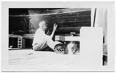 [John R. Frazier working on the hull of a boat]