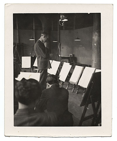 [John R. Frazier reviewing paintings]