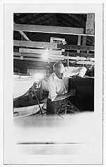 John R. Frazier in a workshop woking on the hull of a boat