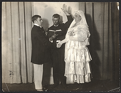 [Wood Gaylor and Robert Ament in wedding attire, performing the wedding ceremony for the Penguin Club's strawberry festival]