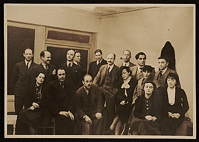 Hugo Gellert and a group of men and women in business attire