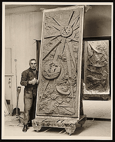 Chaim Gross posing with one panel of his sculpture Six days of creation