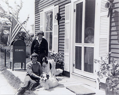[Chenoweth Hall (standing) and Miriam Colwell (seated) in front of post office in Prospect Harbor, Maine, with their dogs Lassie and Stormy]