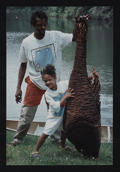[Photograph of Lonnie Holley and child holding artwork]