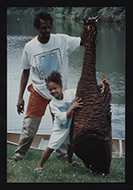 [Photograph of Lonnie Holley and child holding artwork 1]