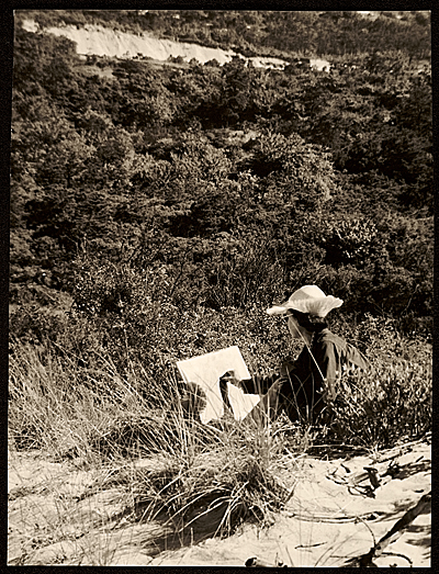 [Female student sketching in the dunes]