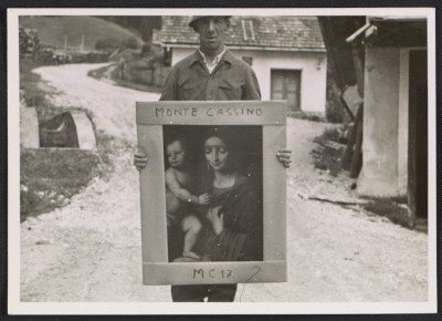Unidentified G.I. holding a painting of the Madonna and child, at Altaussee, Austria