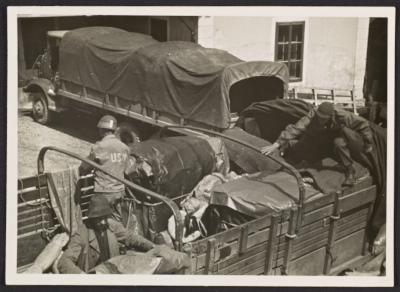 George Stout and two unidentified men loading a truck at Altaussee, Austria