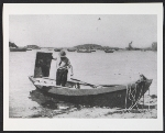 Eric Hudson in a skiff holding a painting