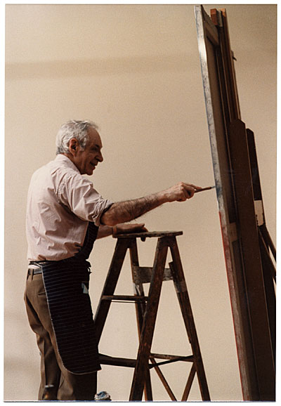 Jacob Kainen on a ladder painting at an easel