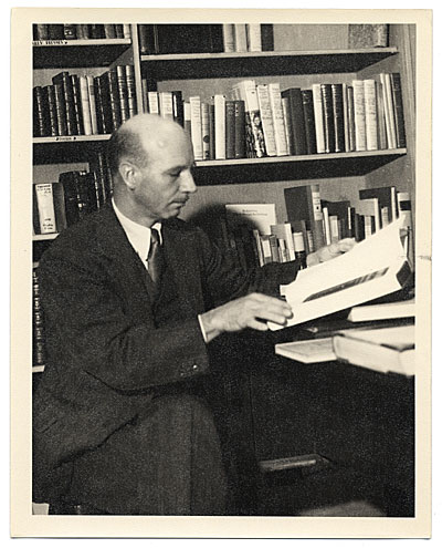 Rockwell Kent at a desk with books