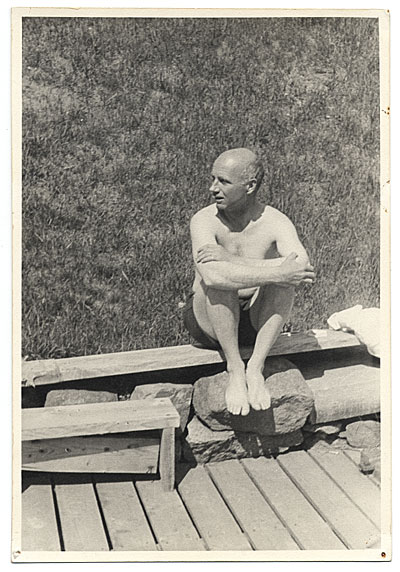[Rockwell Kent sitting on a dock]