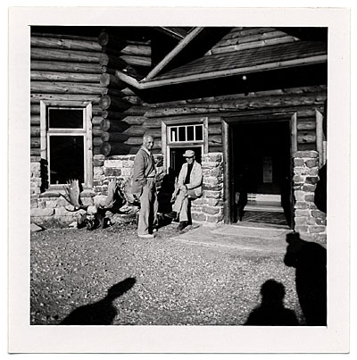 Rockwell Kent outside a stone lodge