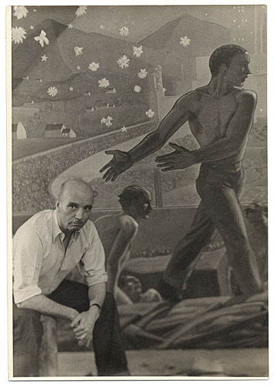 [Rockwell Kent seated next to his mural for the World's Fair]