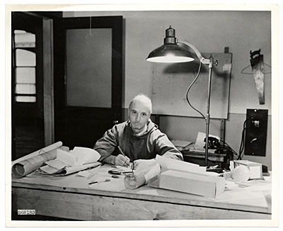 [Rockwell Kent working at his desk]
