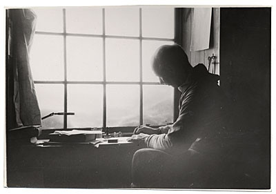 [Rockwell Kent sketching by a window]