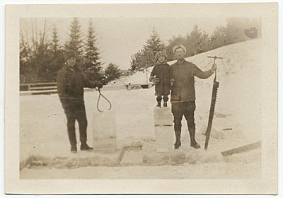Rockwell Kent and another chopping ice blocks from a frozen pond